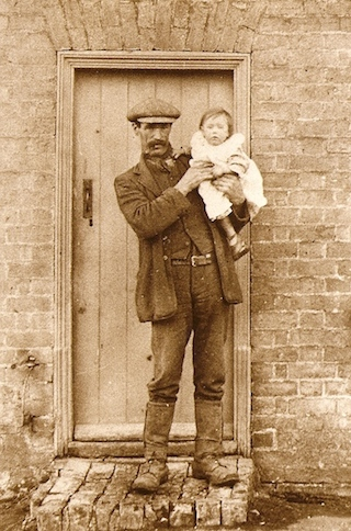 John Pope holding his daughter Audrey outside their home at 239 Main Street, Witchford, circa 1921.